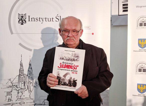 """Zbigniew Bereszyński trzymający książkę Rewolucja """"Solidarności"""" w województwie opolskim 1980-1990"""